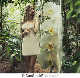 Blonde woman with curly hair among greenery
