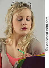 blonde woman with downcast eyes writing