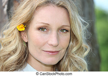 blonde woman with flower in hair