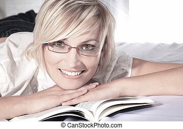 blonde woman with glasses on bed