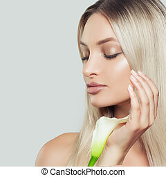Blonde Woman with Healthy Skin and Lily Flowers on White Background. Cosmetology, Beauty and Spa
