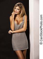 Blonde woman with ideal body wearing grey dress