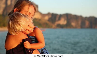 blonde woman with small child admires sunset against cliffs