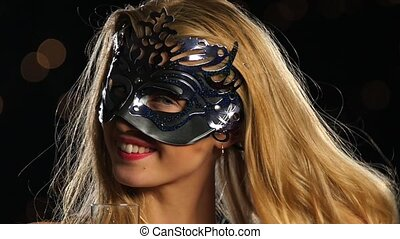 blonde woman with venetian mask and glass of champagne. Slow...