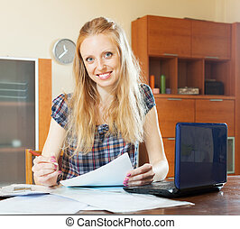 blonde woman working with financial document  at home