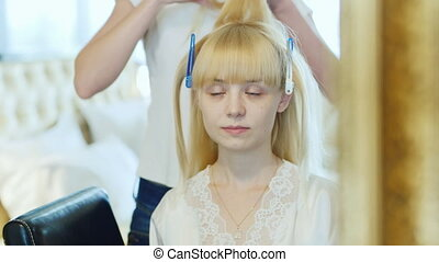 Blonde young bride doing her hair