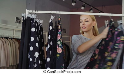 Blonde young lady shopping for clothes, looking through...