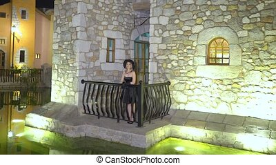 Blonde young woman flirts, seduces, stands on balcony of old...