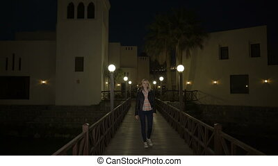 Blonde young woman in leather jacket walks alone on wooden...