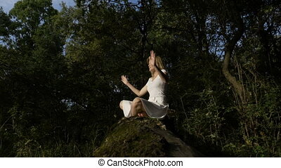Blonde young woman meditating outdoor in lotus yoga position in the forest