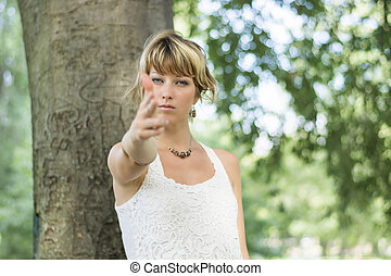 Blonde young woman outdoors pretending to shoot gun with fingers