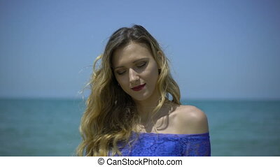 Blonde young woman singing on beach or quay with man...