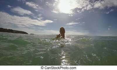 Blonde young woman swimming in the sea