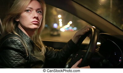young woman driving a car traveling through the city