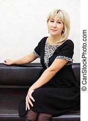 blondin, kvinna, klätt, in, svarting klä, sitt, på, svarta nappa, couch