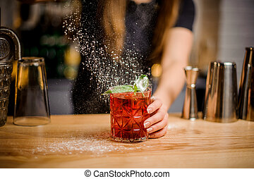 blondy barmaid finishes preparation of cocktail by adding a...