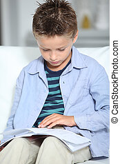 Blong little boy sitting on sofa with book