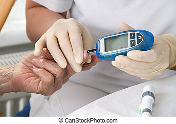 blood glucose meter. the blood sugar value is measured on a...