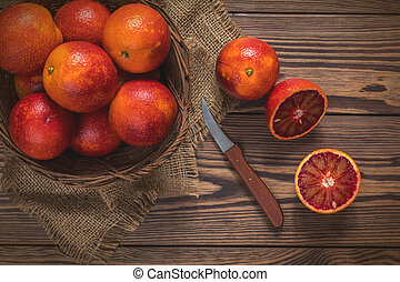 Blood orange fruit in a wicker basket and bottle juice