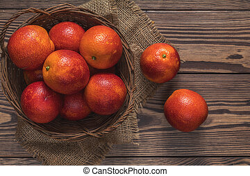 Blood orange fruit in a wicker basket on dark wooden table.