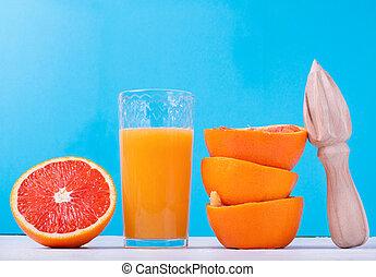 Blood orange juice in the drinking glass on blue