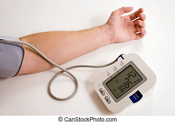 Blood pressure - A man taking his blood pressure using an...