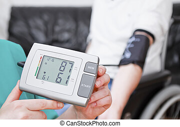 Blood pressure check for young adult in wheelchair.