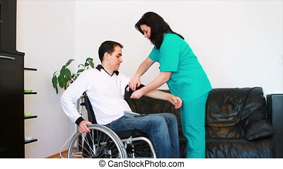 Young man having blood pressure check at home. He is in wheelchair