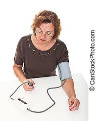 blood pressure check - senior woman check her blodd pressure...