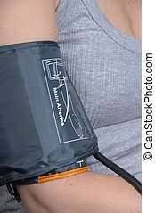 close up of a blood pressure cuff fitted to the right arm of a female patient
