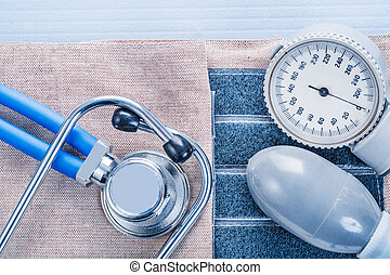 blood pressure monitor and stethoscope  on blue background medic