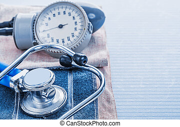 blood pressure monitor and stethoscope on blue background medica