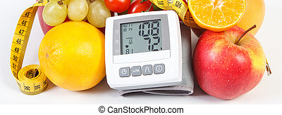 Blood pressure monitor with result of measurement, fresh ripe fruits with vegetables and centimeter, healthy lifestyle