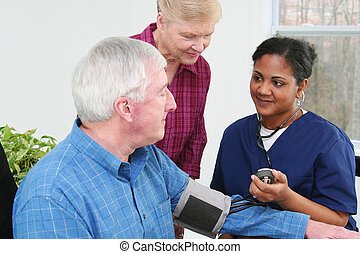 Blood Pressure - Man having his blood pressure checked by a...