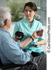 Blood pressure - Young pretty nurse checking the older man's...