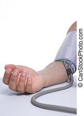 Blood pressure - Woman measuring her blood pressure, against...