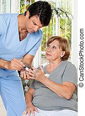 Blood Sugar Test - Male nurse checking sugar level of...