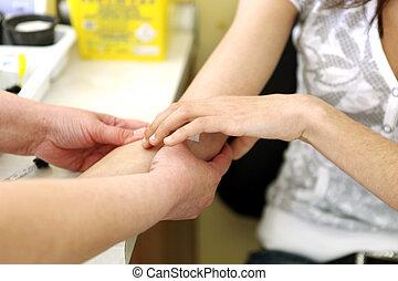 Nurse doing blood sugar test on patient with Diabetes