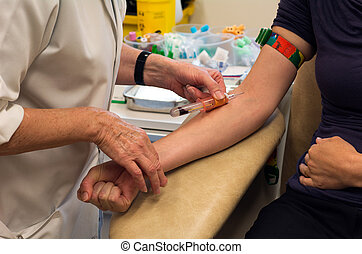 Young woman having blood test in a clinic.