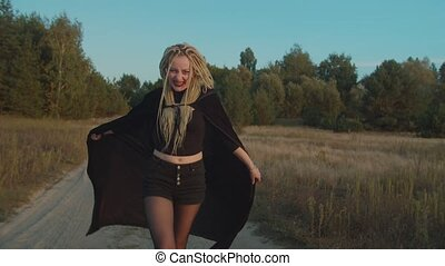 Bloodthirsty creepy female vampire with dreadlocks dressed in black cloak, hungry for blood looking for victim, furiously hissing and frightening while walking on dirt road at twilight.