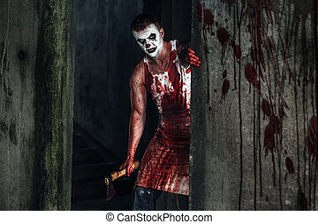 Bloody clown-maniac with ax - Crazy clown holding an ax in...