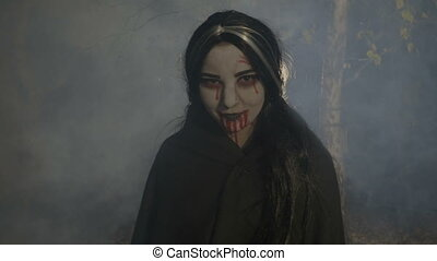 Bloody evil female vampire enjoying the foggy halloween night in the woods and laughing