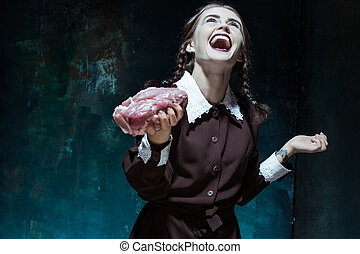 Bloody Halloween theme: crazy girl with raw meat