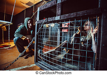 Bloody maniac and his female victim in the cage.
