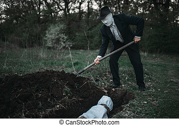 Bloody murderer is digging a grave for the victim