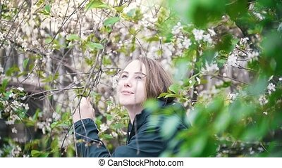 Blooming lilac, girl enjoying the smell of flowers,...