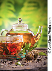 Blooming tea - Cup of tea and teapot with blooming tea on...