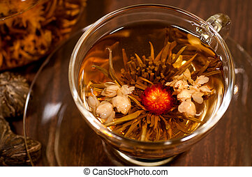Blooming tea with red and white flower close up in a cup