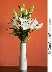 Blooming white lilies in a slim vase on an orange background...