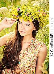 bloomy girl - Romantic girl in a wreath of wild flowers in a...